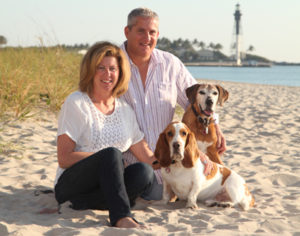 Photo of Rick Magill, CEO of Service Planning Corporation. He is with his wife and two dogs enjoying time outdoors on Florida's coast